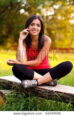Young Girl Sitting Outdoors On Bench