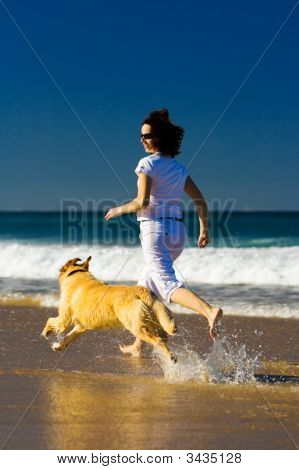 Young Woman And Dog Running On The Beach