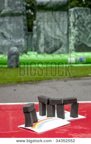 A foam model Stonehenge on a table in front of a life-sized inflatable replica of Stonehenge