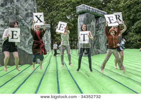 : Teenagers bouncing and holding up letters that spell out