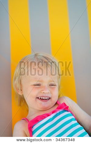 Portrait Of Laughing Baby Laying On Sunbed