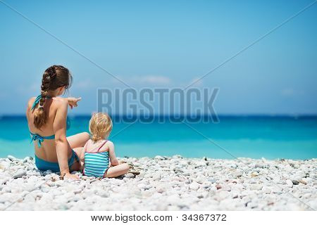 Mother Sitting With Baby On Sea Shore Looking Into Distance. Rea