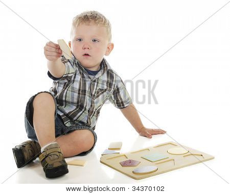 A young preschooler trying to figure out where the hexagon goes in his wooden shape puzzle.  On a white background.