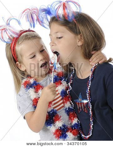 An adorable preschooler giving her sister a lick of her lollipop.  Both girls are decked out for celebrating America's Independence Day.  On a white background.