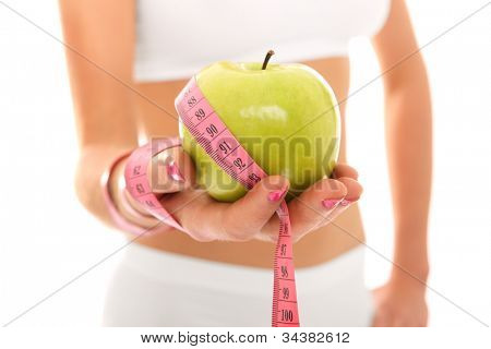 A picture of a young fit woman showing a green apple and a measure tape over white background