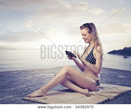 Smiling beautiful young woman sitting on a bath towel at the seaside and using a tablet pc