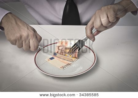 Businessman's hands cutting a banknote in a dish with fork and knife