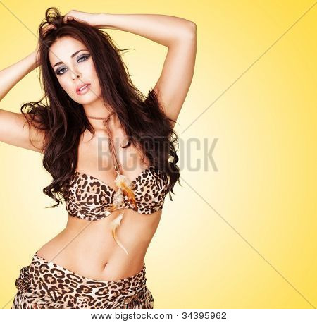 Sexy curvy woman with a bare belly wearing an animal print summer outfit posing against a yellow studio background with copyspace