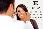 picture of ophthalmology  - Woman wearing glasses after taking a vision test at the doctor - JPG