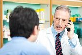 stock photo of erectile dysfunction  - Chemist at phone while dealing with a customer - JPG