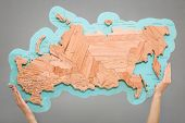 The Girl Holds In Her Hands A Map Of Russia, Made Manually From Different Species Of Wood. Decor For poster