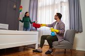 Woman Is Angry Because Her Husband Is Lazy And Avoids Cleaning Apartment. poster