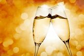 stock photo of sparkling wine  - Two elegant champagne glasses on golden background - JPG