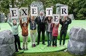 The Right Worshipful the Lord Mayor of Exeter Rob Newby stands with children who hold up letters th