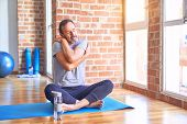 Middle age handsome sportman sitting on mat doing stretching yoga exercise at gym Hugging oneself ha poster