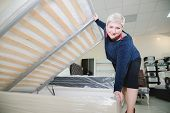 Portrait. Adult Stylish Woman, Short-cut Blonde, Chooses A Large Orthopedic Bed With A Lifting Mattr poster