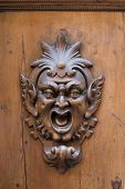 stock photo of gruesome  - Carved gargoyle adorning a wooden door in Siena Italy - JPG