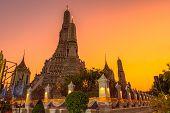 Large illuminated temple Wat Arun after sunset seen accross river Chao Phraya Bangkok, Thailandgold poster