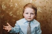 Closeup Portrait Of A Boy. Funny Closeup Portrait Of Emotional Boy In A Blue Shirt With A Tie. True  poster