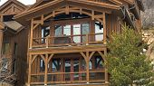 Pano Exterior Of Cabin In Park City Utah With Brown Wood Exterior Wall And Balconies poster