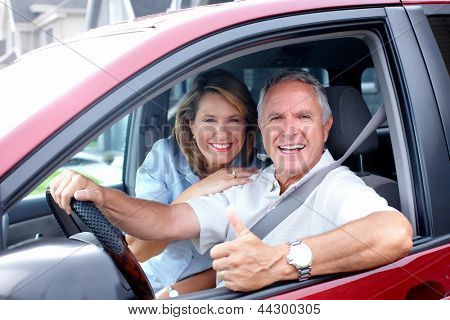 Happy senior couple in the car. Transportation.
