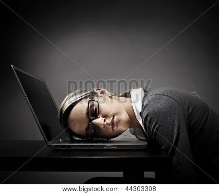 Tired woman student sleeping on laptop computer.