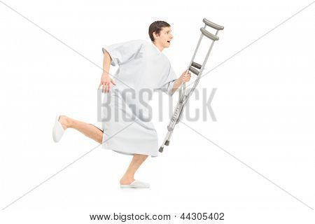 Full length portrait of a male patient running and holding a crutch, isolated on white background