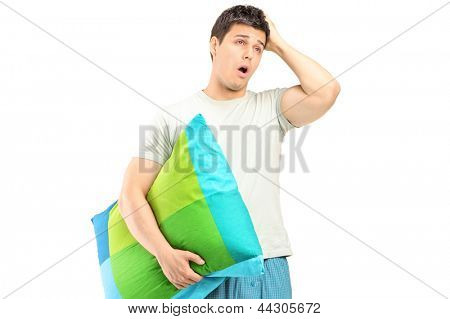 A young man in pajamas feeling sleepy isolated on white background