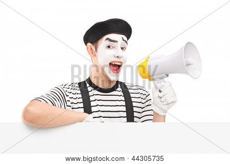 Male mime artist holding a loudspeaker and posing on a blank panel, isolated on white background