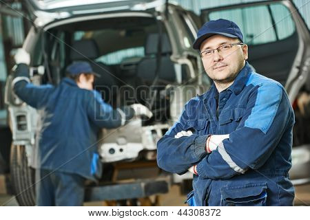 automobile repairman worker portrait in automotive industry in front of car under repair