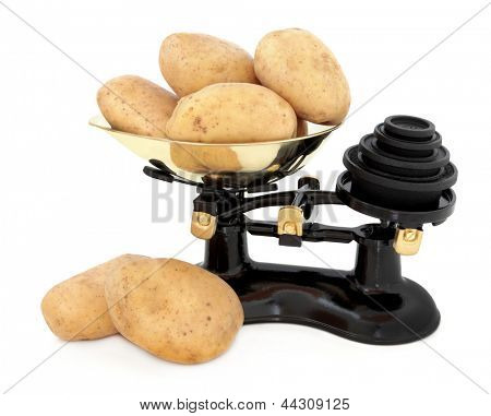 Baking potato stack in a retro cast iron set of scales with brass weights over white background.