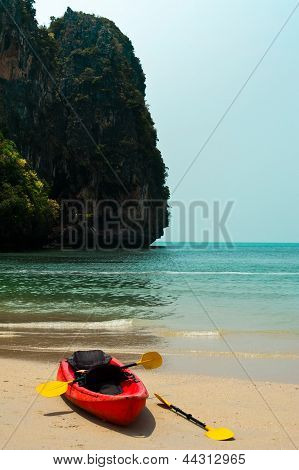 Tropical Beach Landscape With Red Canoe Boat At Ocean Gulf Under Blue Sky