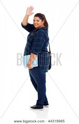 full length of cheerful overweight student waving goodbye isolated on white background