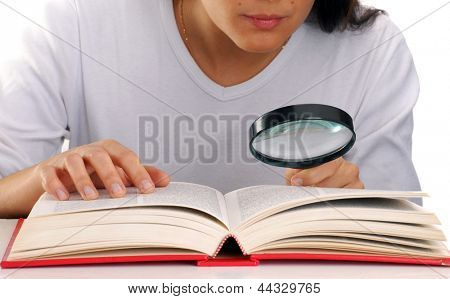 Young woman holding a magnifying glass reading a book.