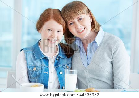 Lovely girl and her mother looking at camera with smiles