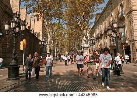BARCELONA - OCTOBER, 5: Tourists strolling famous Ramblas on October 5, 2009 in Barcelona, Spain. Rambla boulevard is one of the most recognized streets in the world.