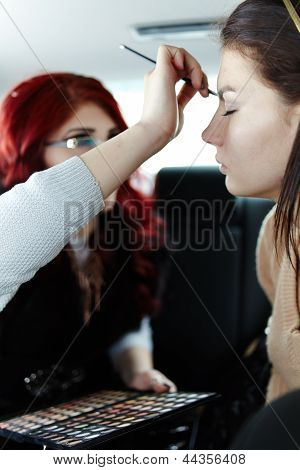 Woman Having Makeup Applied On The Backseat Of The Car