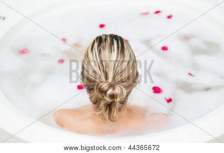 Back of blonde woman taking a foam bath