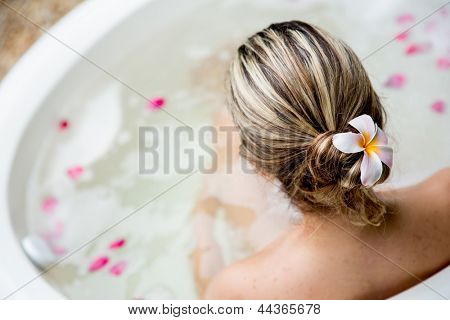 Back of woman in a bathtub and a flower in her hair