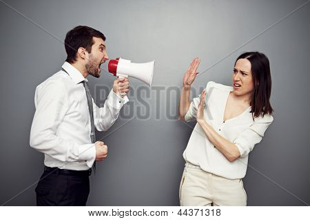 angry boss screaming in megaphone at the woman. studio shot over dark background