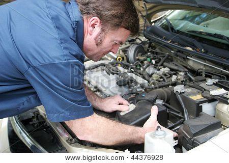 Mecánico de automóviles bajo el capó, trabajando en un motor de coche.