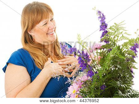 Pretty blond woman receiving a beautiful bouquet of flowers.  Isolated on white.