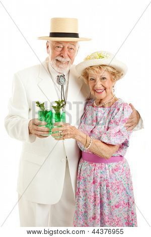 Kentucky Colonel and his wife dressed up and drinking mint juleps in celebration of Kentucky Derby Day.  Isolated on white.