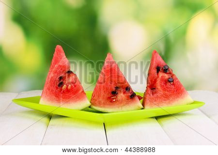 Sweet watermelon slices on plate on wooden table on natural background