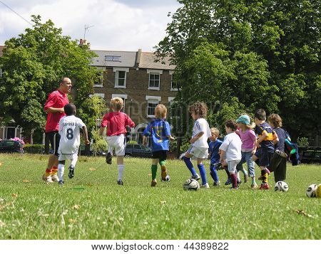 Little kids on football training in the park