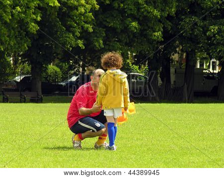 Football coach is talking to a little player