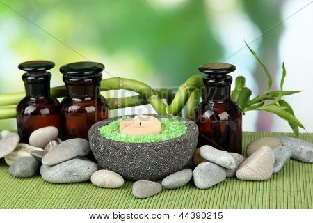 Still life with green bamboo plant and stones, on bamboo mat, on bright background