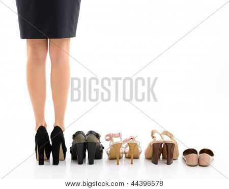 Shopping and sale. Female legs with shoes assortment, young woman put shoes on in shop and makes her choice, back view. Over white background