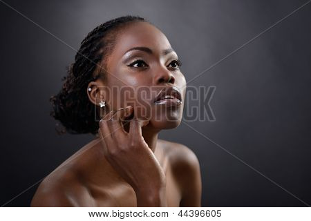 Beautiful young african woman posing at studio, face with hand portrait over dark background