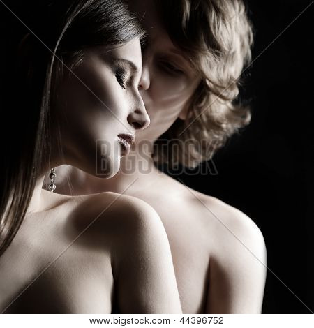 Sexy passion couple, beautiful young man and woman in love closeup, studio shot over black